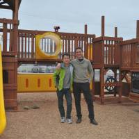 Job well done: Michael Anop puts his arm over the shoulder of Ron Choi, one of his project's supporters, at a completed playground in Minamisoma, Fukushima Prefecture. | EMIKO MANNERS