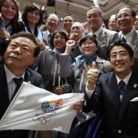 Pass the pork, cue the crackdown: Prime Minister Shinzo Abe (thumbs up), Tokyo Gov. Naoki Inose (left) and members of the capital's Olympic delegation celebrate the city's selection as host of the 2020 Olympic Games, in Buenos Aires on Sept. 7. | AP