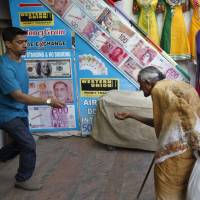 Hanging on: An employee at a foreign currency exchange outlet gives alms to a beggar in Bangalore, India, on Friday. India assured foreign investors the same day it is not contemplating capital controls as a step to stabilize the falling rupee. It also released new growth figures that showed its economic slowdown had deepened. | AP