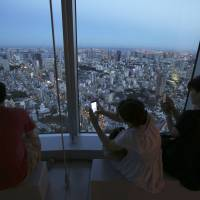 Lots to see: People photograph Tokyo with smartphones from Roppongi Hills Mori Tower at dusk Monday. Tokyo is vying with Madrid and Istanbul for the right to host the 2020 Olympics. | AP