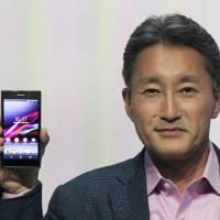 Hold the phone: Sony Corp. Chief Executive Officer Kazuo Hirai holds the company's new Xperia Z1 smartphone, featuring an improved lens to boost camera performance, at a press event in Berlin on Wednesday. | KYODO