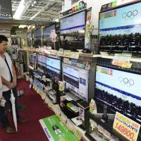 Upgrade time: Customers admire widescreen TVs in Akihabara, Tokyo's tech mecca, Sunday morning.  | KYODO