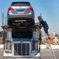 Locked and loaded: A Nissan Rogue is loaded onto a car carrier at the Port of Los Angeles for dealer delivery on June 28. Nissan said Tuesday it has revamped the popular SUV to get a bigger share of the growing crossover segment. | BLOOMBERG
