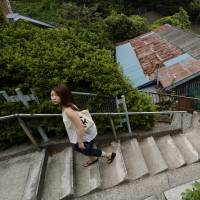A young woman climbs a concrete stairway beside houses in the same area last month. | BLOOMBERG