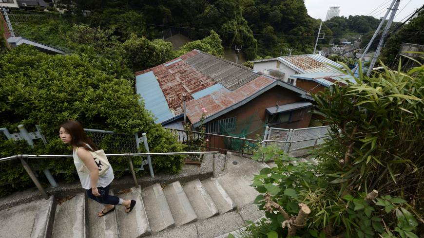 A young woman climbs a concrete stairway beside houses in the same area last month.