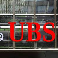 Paying up: The UBS AG company logo is seen at the bank's headquarters in Zurich. | BLOOMBERG