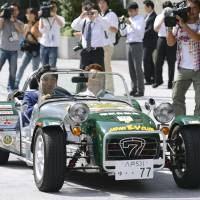 Off to the races: Senior Vice Industry Minister Isshu Sugawara (left) and Tadashi Tateuchi, head of the Japan Electric  Vehicle Club, ride a British Caterham Super Seven sports car that runs on electricity in Tokyo on Tuesday. | KYODO