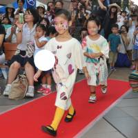 Child's play: Kids take part in a fashion show during Children's International Festa 2013 in Shibuya Ward, Tokyo, on Saturday. While at the Brazilian Embassy booth, kids get soccer tips. | YOSHIAKI MIURA