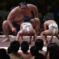 Two on one: A Japanese sumo teacher engages in a mock match with two children during an exhibition before a two-day sumo tournament in Jakarta on Aug. 24. | AFP-JIJI
