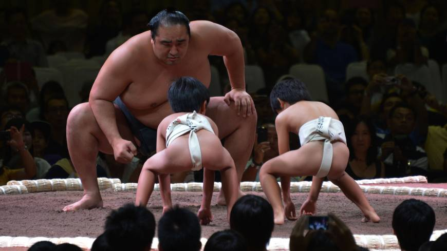 Two on one: A Japanese sumo teacher engages in a mock match with two children during an exhibition before a two-day sumo tournament in Jakarta on Aug. 24.