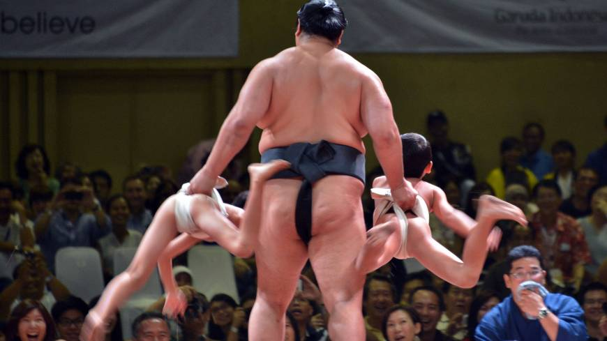 Cry uncle: A sumo wrestler playfully holds up two young boys during an exhibition in Jakarta on Aug. 24.