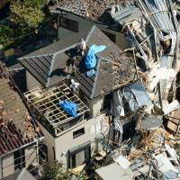 Twister toll: Residents clear debris Tuesday morning in Koshigaya, Saitama Prefecture, after a tornado swept through the previous day, wreaking havoc on hundreds of buildings and injuring dozens of people. | KYODO