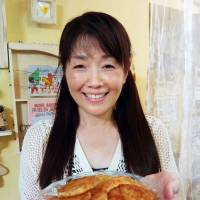 Nothing wasted: Seiko Tabata, a craft artist living in Akishima, Tokyo, shows off pancakes she made from leftover rice. | KYODO