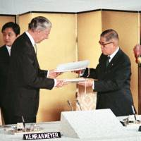 A file photo show U.S. Ambassador to Japan Armin Meyer (left) and then Foreign Minister Kiichi Aichi exchanging signed documents on the agreement on returning the Ryukyu Islands and Daito Islands between the two countries in June 1971. | KYODO