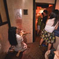 Summer chill: Visitors react in The Cursed Tooth, a haunted house at Tokyo Dome City Attractions, on Aug. 15. | AFP-JIJI