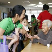 Generations: A resident at a senior care center in Kobe interacts with a visiting mother and her young child in May. | KYODO