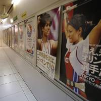Cash in!: Official posters promoting Tokyo's bid for the 2020 Olympics hang on the wall of a subway concourse in Tokyo on Wednesday. | AP