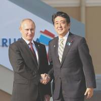 Comrades: Russian President Vladimir Putin welcomes Prime Minister Shinzo Abe in St. Petersburg on Thursday. | KYODO