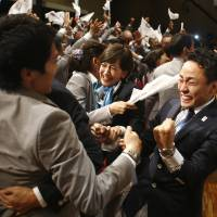Members of the Tokyo delegation celebrate in Buenos Aires Saturday. | AP