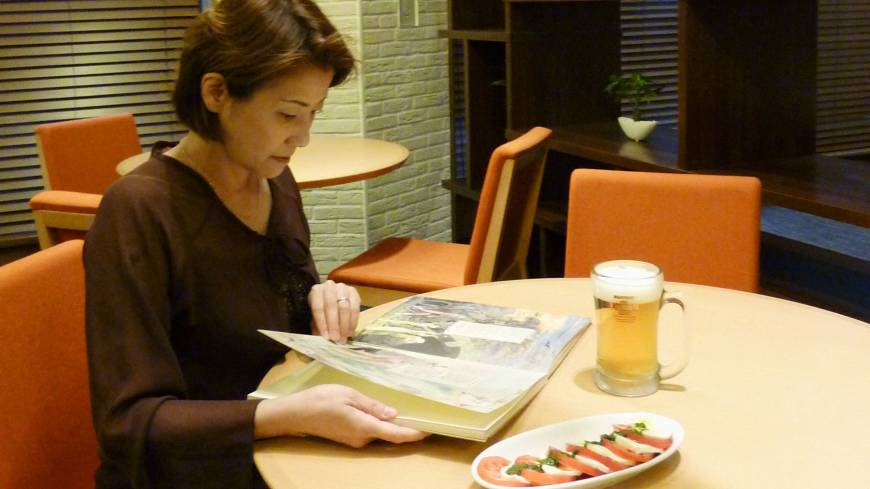 Drinking it in: A woman reads a book over a mug of beer at a restaurant in the Hibiya Library & Museum in Chiyoda Ward, Tokyo, on July 26.