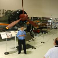 One of a kind: Takashi Amano, head of the archives room at Mitsubishi Heavy Industries' Komaki-Minami plant, tells visitors about the Imperial Japanese Navy's Zero fighter plane. | CHUNICHI SHIMBUN