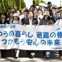 United front: Plaintiffs suing Tokyo Electric Power Co. over the Fukushima nuclear accident that forced them to seek refuge in the Kansai region hold a banner Tuesday outside the Osaka District Court emphasizing their desire to return to 'normal life.' | KYODO