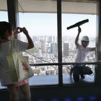 Something to see: A woman visiting the special observation deck at Tokyo Tower in Minato Ward photographs a window cleaner on Tuesday. A broken window on an elevator serving the deck, 250 meters above ground, forced a shutdown the same day. | AP