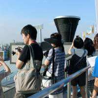 Up close and personal: People taking a tour of National Olympic Stadium in Shinjuku Ward, Tokyo, take in a great view of the Olympic cauldron on Sept. 12. | KYODO