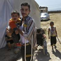 Out of harm's way: Syrian refugee Mohammed Ahmed, 20, carries his son at a temporary refugee camp in the eastern Lebanese Town of Al-Faour in the Bekaa Valley near the border with Syria on Wednesday, after fleeting his home in Baba Amro, Homs province. | AP