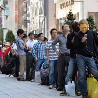 A long line waits outside Apple's store in Tokyo's Ginza district Friday morning to buy the latest versions of the popular handsets. | AFP-JIJI
