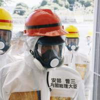 Tepco'ed: Prime Minister Shinzo Abe wears a protective suit with his surname misspelled as he inspects the Fukushima No. 1 plant on Thursday. | KYODO