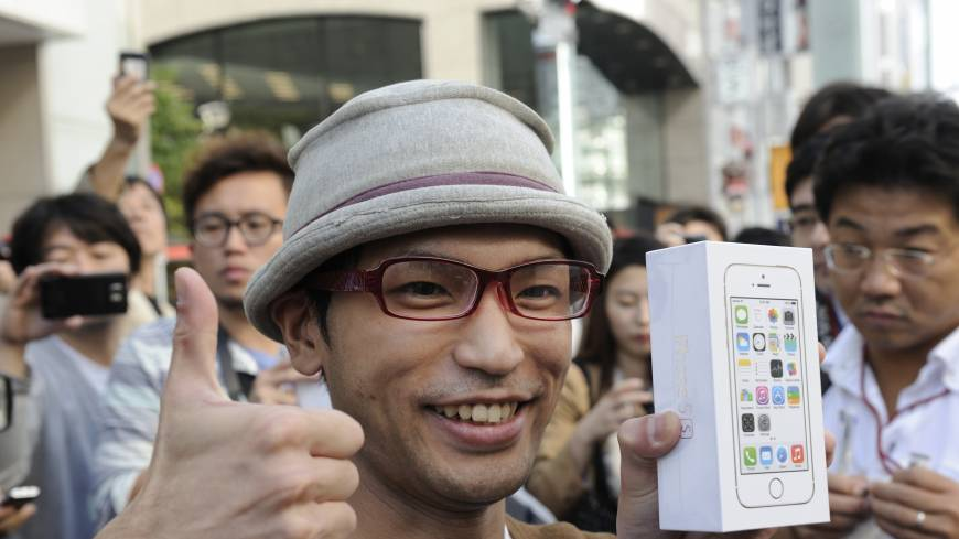 Top of the line: The first customer who purchased the iPhone 5S at the company's flagship store in Ginza gives a big thumbs up.