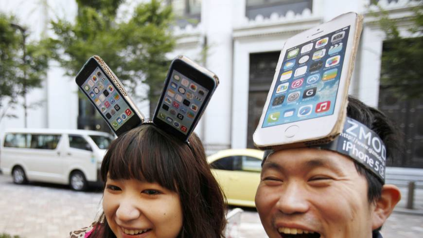 A step ahead: Yui Kashima, left, and Nobuhiko Matsuda, sport handmade iPhone headgear as they wait in line Friday to buy Apple's new iPhone 5 outside a store in Tokyo.