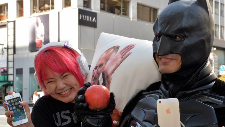 Batty about Apple: True fans display their newly purchased iPhones in Tokyo Friday.