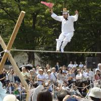 Delicate balance: A South Korean performer walks a tightrope Saturday during a cultural-exchange event held at Hibiya Park in Tokyo. | KYODO