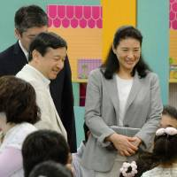 Life goes on: Crown Prince Naruhito and Crown Princess Masako watch children play at a nursing facility in the city of Koriyama on Sunday while visiting earthquake and tsunami victims in Fukushima Prefecture. | KYODO