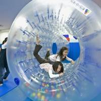 Tots in toys: Children play inside a clear plastic wheel at a Kid-o-Kid play space in Kawasaki operated by BorneLund Inc. | BORNELUND INC./KYODO