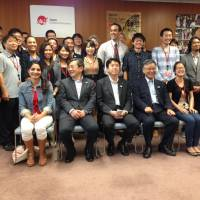 Tourist snapshot: International students pose for a photo with senior vice tourism minister Yosuke Tsuruho (seated, center) and others following a roundtable meeting on Japan's tourism strategy Wednesday in Tokyo. | JUN HONGO