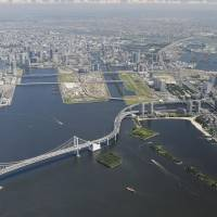 In the way: The Rainbow Bridge is seen in Tokyo Bay on Aug. 28. The landmark's low clearance height of 52 meters is frustrating Tokyo officials eager to lure today's giant cruise ships to the capital during the 2020 Olympics. | KYODO