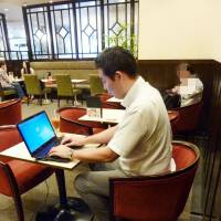 Power-hungry: A customer works on a laptop plugged into an outlet at a Renoir coffee shop in Shinjuku Ward, Tokyo. | KYODO