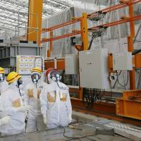 Cleaning machine: Prime Minister Shinzo Abe (right) looks at the ALPS water-decontamination system during a tour of the Fukushima No. 1 plant on Sept. 19. Testing of the system, which is key to removing radioactive contaminants from water that was stored after cooling the reactors, is to resume Friday. | KYODO