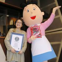 Voice behind the face: Midori Kato, who dubs the voice of cartoon character 'Sazae-san' on the animated TV series of the same name, poses earlier this month with a mascot of the character. | KYODO
