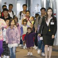 Yokoso Japan: Four Myanmar families from a refugee camp in Thailand arrive at Narita airport Friday evening to begin their new lives in Japan under a U.N. resettlement program. | KYODO