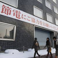 Old threat: A banner at the headquarters of Hokkaido Electric Power Co. in Sapporo in December asks residents to save power last winter. Utilities won't be setting numerical power-saving targets this year as they've returned to life without atomic power since the 2011 core meltdowns in Fukushima. | KYODO
