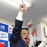 Triumphant: Osami Takeyama celebrates his re-election Sunday night as mayor of Sakai, Osaka Prefecture. | KYODO