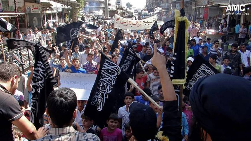 Sectarian slide: Anti-Syrian regime protesters hold al-Qaida flags with Arabic writing that reads, 'There is no God but Allah and Mohammed is his messenger,' as they chant slogans during a demonstration in Aleppo, northern Syria, on Friday.