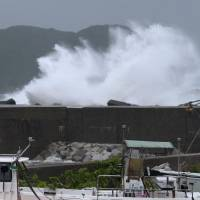 Making waves: High waves crash into a breakwater in Kumano, Mie Prefecture, Sunday afternoon as Typhoon Man-yi made its way toward Honshu.  | KYODO