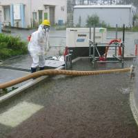 Rain, rain, go away: A worker pumps out radioactive water accumulating inside the barriers around a leaky coolant storage tank at the Fukushima No. 1 nuclear plant Sunday, the day before Typhoon Man-yi swept through Honshu, including the Tohoku region. 
