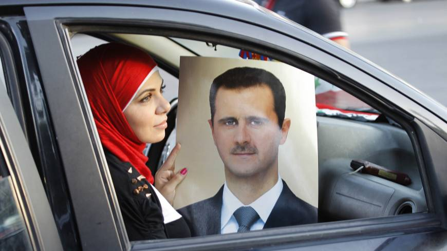 Party line: A Syrian woman holds a portrait of President Bashar Assad as pro-regime supporters celebrate Assad's 48th birthday in Damascus on Tuesday.