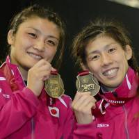 Midas touch: Kaori Icho (left) and Saori Yoshida hold their medals after winning gold at the world wrestling championships in Budapest on Thursday.  | KYODO
